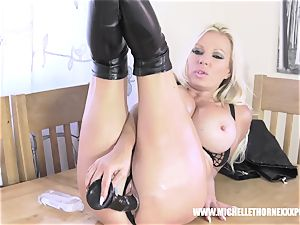 Oily towheaded biker babe strokes with a thick dark-hued toy